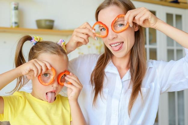 Madre e figlio che preparano cibo sano e si divertono tengono un peperone davanti ai loro occhi