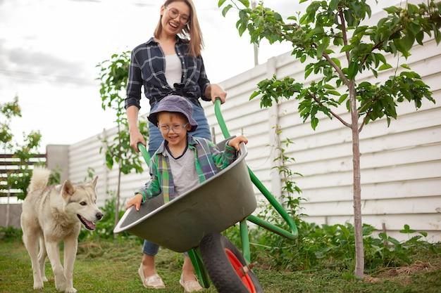 Madre e figlio cavalcano un carretto da giardino divertendosi nel giardino sul retro
