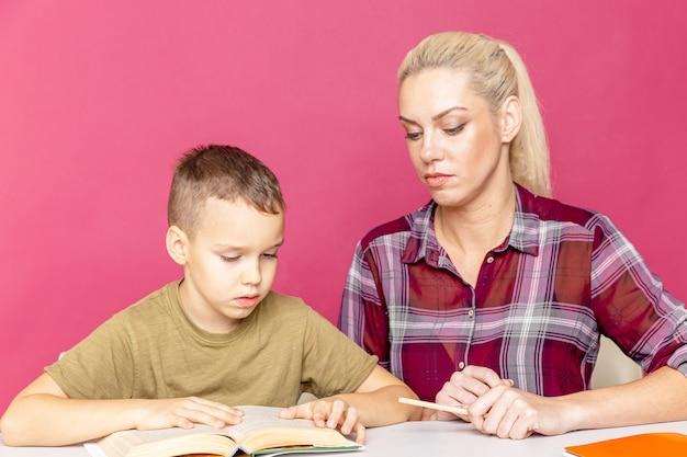 Madre e figlio che fanno i compiti a scrivere e leggere a casa. istruzione domiciliare in quarantena.