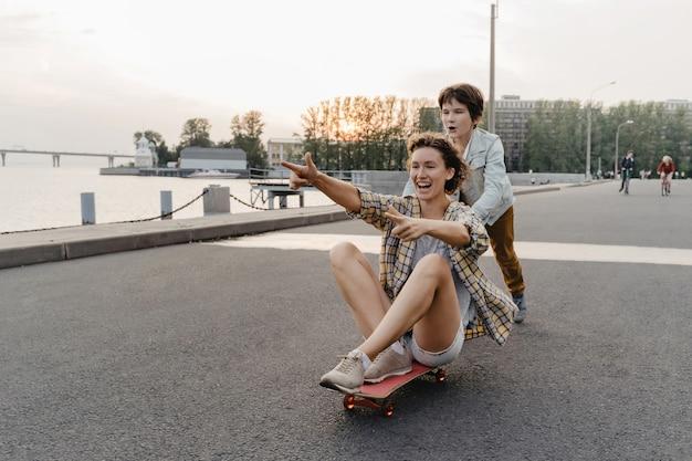 Madre e figlio che trascorrono il loro tempo libero facendo skateboard all'aperto