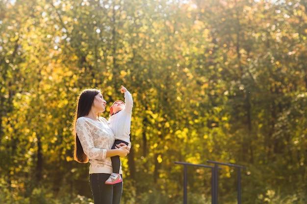 Madre e figlio camminano sera nel parco, calda luce del sole