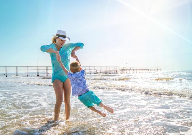 Madre e bambini stanno giocando nel mare sulla spiaggia