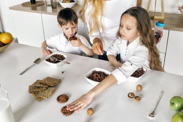 I bambini della madre mangiano la prima colazione cucina domestica famiglia amorosa felice