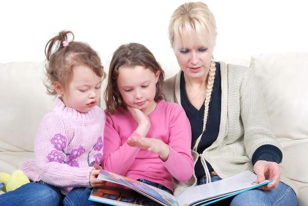 Madre e bambini seduti in soggiorno a leggere un libro
