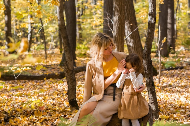 Madre che conforta la sua bambina che piange nelle emozioni della natura autunnale e nel concetto di famiglia