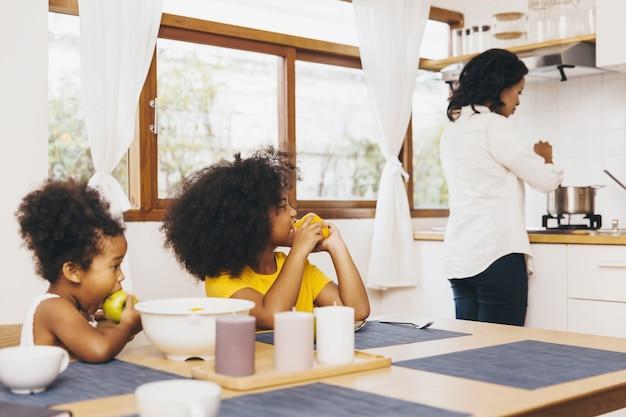Madre che cucina per i suoi due figli in attesa del pranzo. concetto di mamma single.