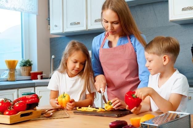 Madre che cucina con i suoi figli in cucina