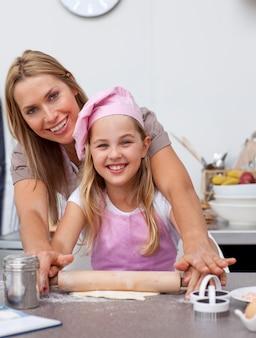 Madre e figlia che cuociono i biscotti di natale in cucina
