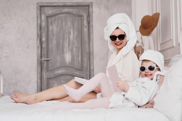 Madre e figlia in camera da letto in accappatoio leggono riviste