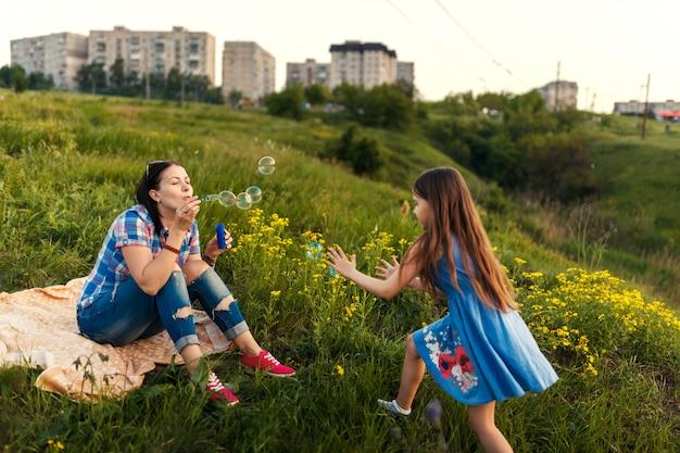Madre e figlia soffiando bolle di sapone