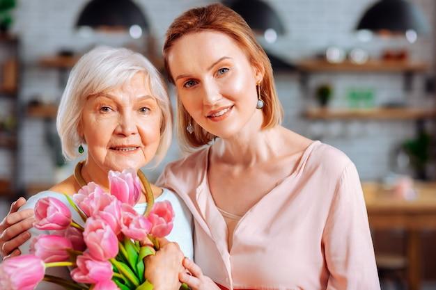 Legame madre-figlia. attraente signora matura dai capelli rossi in camicetta rosa a blocchi di colore coccole invecchiata bella mamma dai capelli bianchi rugosa con mazzo di tulipani