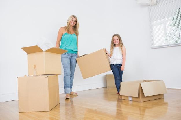 Madre e figlia che trasportano scatole movimento