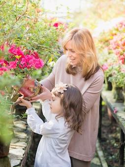 Madre e figlia che trasportano piante, giardinaggio in serra.
