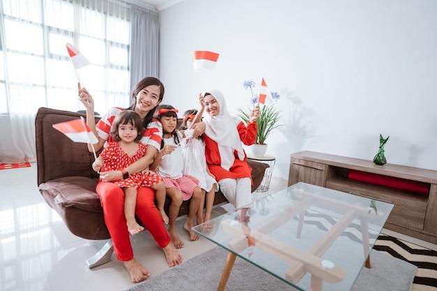 Madre e figlia che celebrano il giorno dell'indipendenza indonesiana a casa vestite di rosso e bianco con ind...
