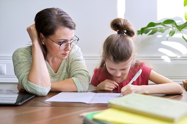 Madre e figlia studiano insieme a casa, seduti a tavola, la ragazza scrive sul taccuino. apprendimento a distanza, genitore che aiuta bambino studente di scuola primaria