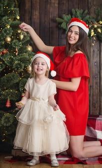 Madre e figlia all'albero di natale su un fondo di legno