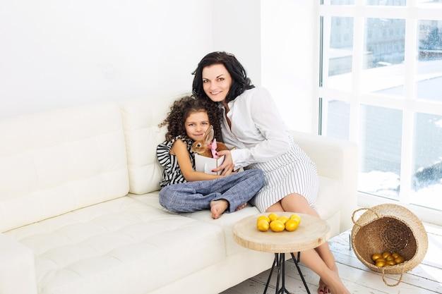 Madre e figlia carine, belle e felici con i conigli e le uova di pasqua a casa insieme