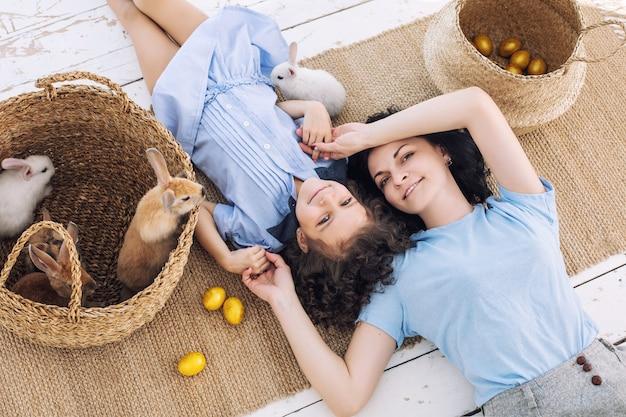 Madre e figlia carine, belle e felici con conigli e uova di pasqua in cesti di vimini insieme