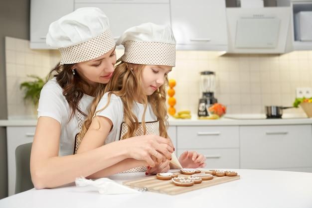 Madre e figlia che decorano i biscotti dello zenzero.