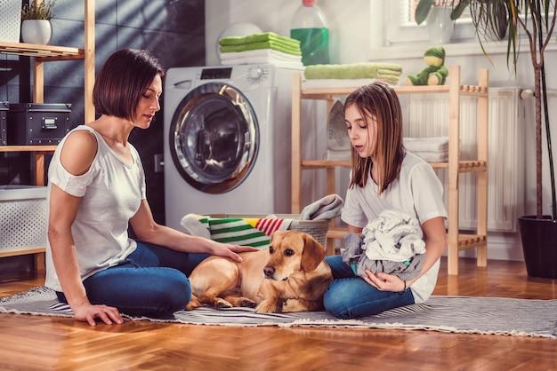 Madre, figlia e cane che parlano e selezionano la biancheria sul pavimento Foto Premium