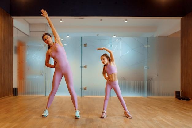 Madre e figlia che fanno esercizio in palestra, allenamento fitness. mamma e bambina in abbigliamento sportivo, allenamento congiunto nel club sportivo