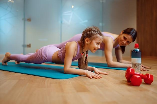 Madre e figlia che fanno esercizio di stampa su stuoie in palestra, allenamento yoga. mamma e bambina in abiti sportivi, donna con bambino, formazione congiunta in club sportivo