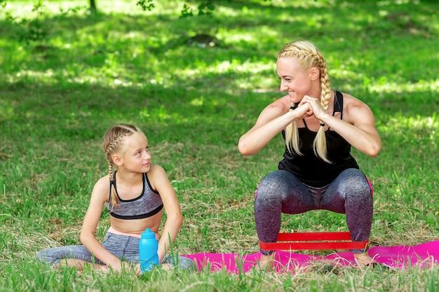 Madre e figlia che fanno esercizi sportivi sul tappeto nel parco all'aperto