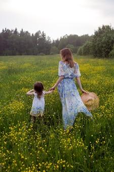 Madre e figlia in abiti e cappello stanno in un campo di fiori gialli nel giorno d'estate