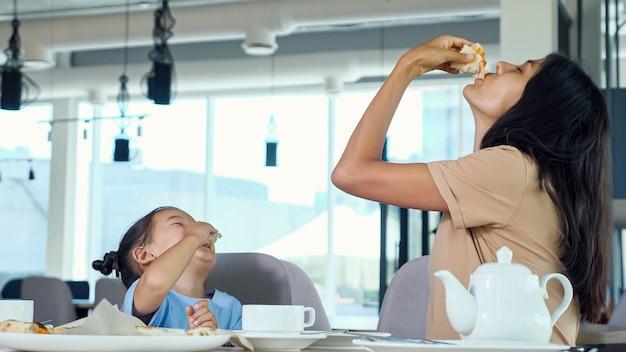 Madre e figlia mangiano la pizza. la mamma asiatica allegra con i capelli lunghi e sciolti e la bambina mangiano uno spuntino delizioso al tavolo di legno nella vista ravvicinata del bar
