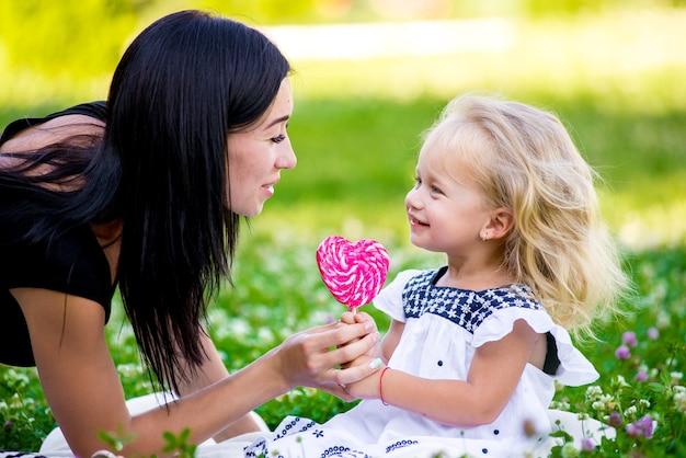 Madre e figlia che mangiano caramelle dolci su un bastone