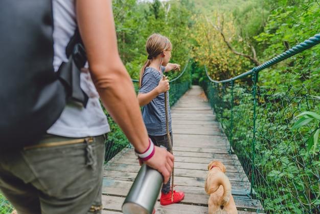 Madre e figlia nella foresta che camminano sopra il ponte di legno