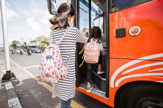 Madre e figlia che vanno a scuola la mattina con l'autobus pubblico
