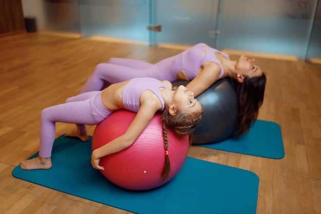 Madre e figlia in palestra, esercizio di pilates sulle palle, allenamento yoga.