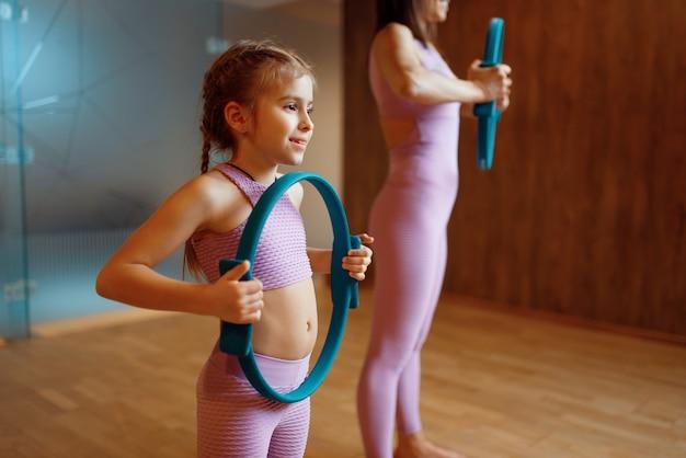 Madre e figlia in palestra, esercizio di pilates con anelli, allenamento yoga. mamma e bambina in abiti sportivi, donna con bambino in formazione congiunta in club sportivo