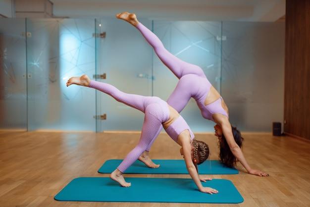 Madre e figlia in palestra, esercizio di stretching in movimento, allenamento yoga. mamma e bambina in abiti sportivi, donna con bambino in formazione congiunta in club sportivo