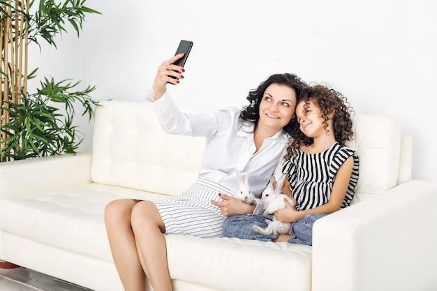 Madre e figlia felici con soffici conigli seduti su un divano bianco e facendo selfie sul cellulare