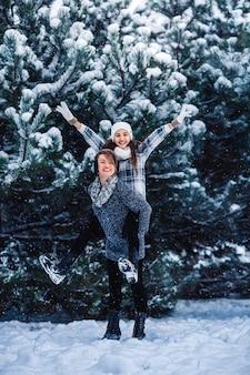 Madre e figlia si divertono a giocare nella foresta invernale.