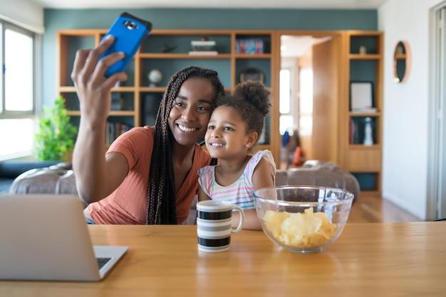 Madre e figlia che si divertono insieme e fanno un selfie con il cellulare mentre si resta a casa. concetto monoparentale. nuovo concetto di stile di vita normale.