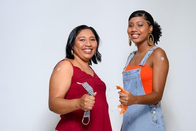 Madre e figlia tengono la maschera facciale e sorridono felici e mostrano il segno del vaccino sul braccio senza