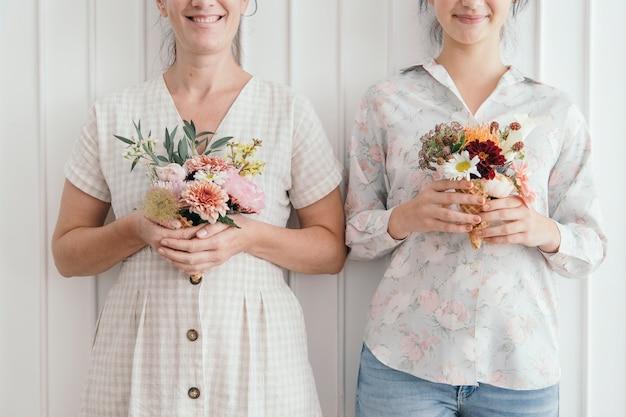 Madre e figlia che tengono fiori in coni gelato