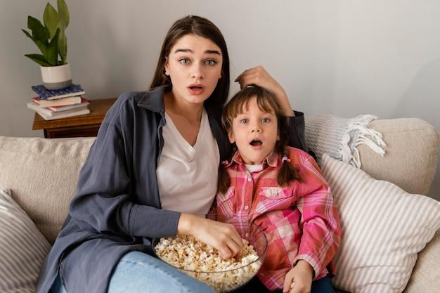 Madre e figlia a casa a mangiare popcorn