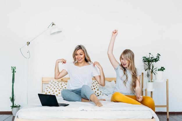 Madre e figlia a casa con il computer portatile