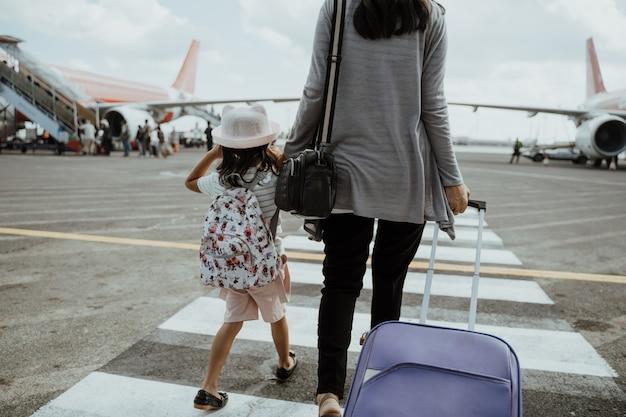 Una madre e una figlia si uniscono per mano camminando con una valigia