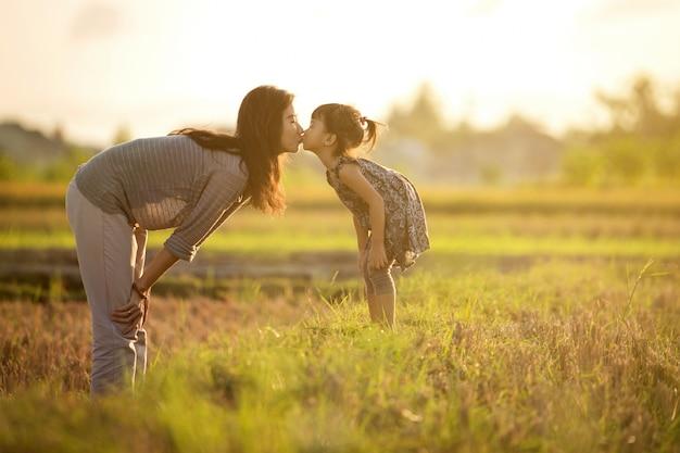 Madre e figlia che baciano nel campo