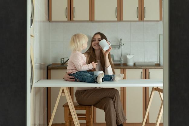 Madre e figlia in cucina. la giovane mamma e il bambino felici fanno colazione a casa.