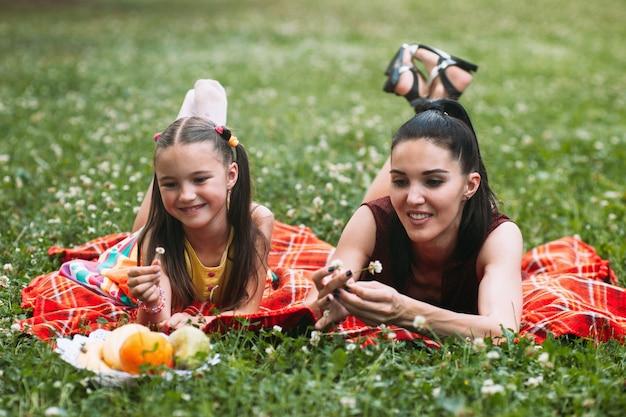 Relazione amorevole madre e figlia. famiglia al picnic al parco naturale