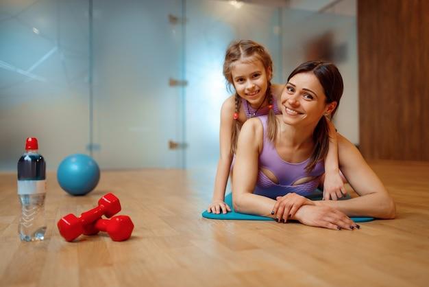 Madre e figlia sdraiate sul tappetino insieme in palestra, allenamento fitness, ginnastica. mamma e bambina in abbigliamento sportivo, allenamento congiunto nel club sportivo