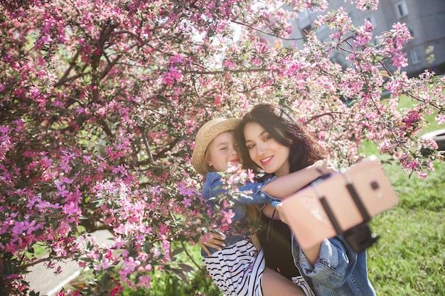 Madre e figlia che fanno selfie al parco. ragazze che sparano sul telefono cellulare