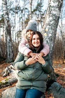 Madre e figlia nella natura, nella foresta o nel parco, camminano nella comunicazione e nella salute