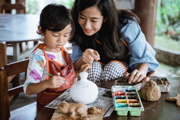Madre e figlia che dipingono vaso di ceramica